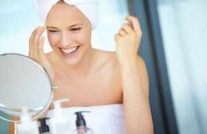 Woman-applying-makeup-in-mirror