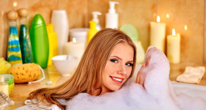 Happy smiling woman taking bath with a lot of foam.