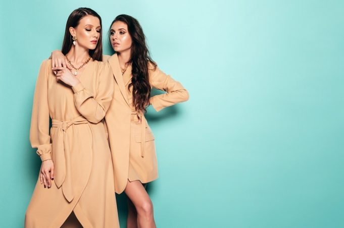 Two young beautiful brunette girls in nice trendy summer clothes.Sexy carefree women posing near blue wall in studio.Fashionable models with bright evening makeup.They hug and touch each other