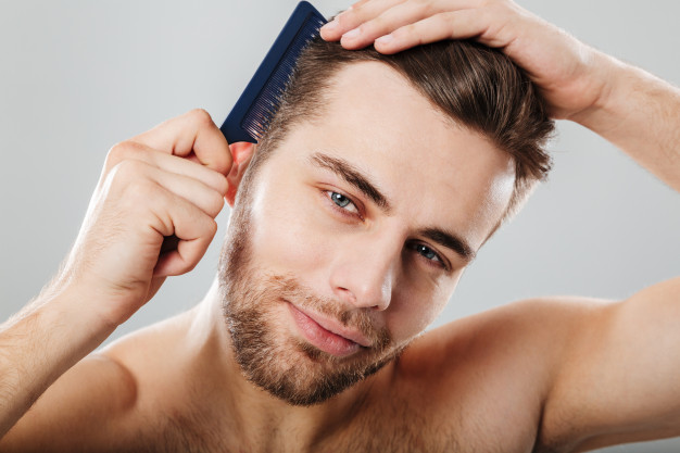 close-up-portrait-smiling-man-combing-his-hair_171337-2953