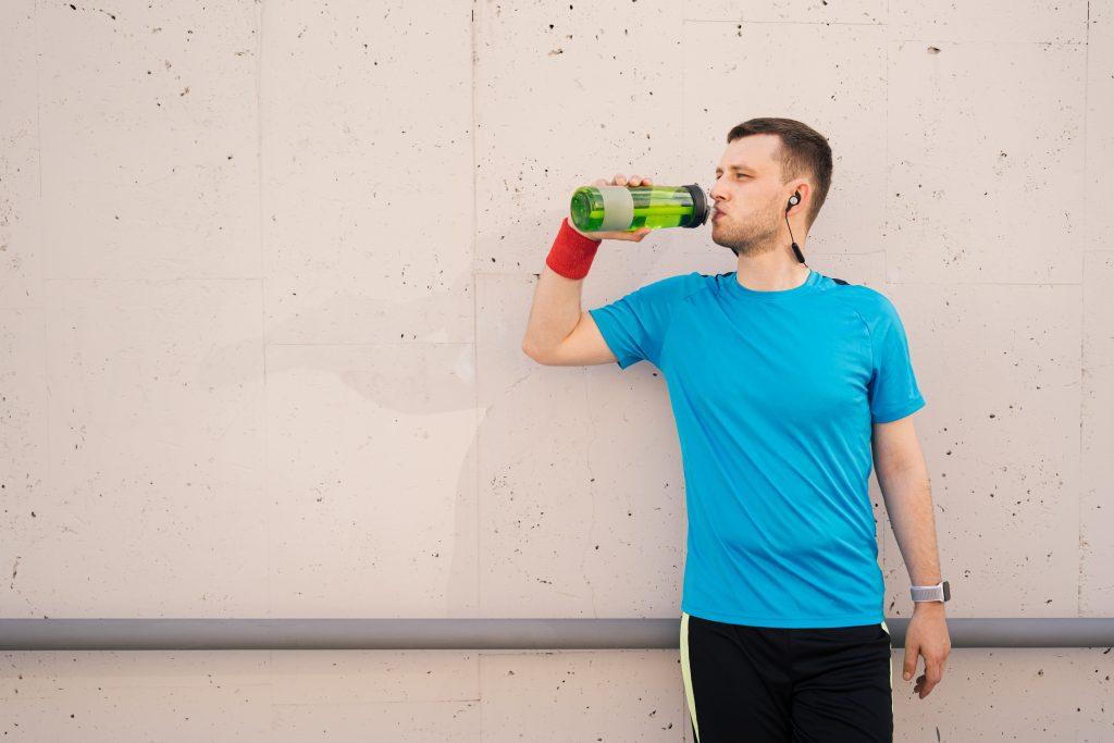 Caucasian man drinking water during exercises
